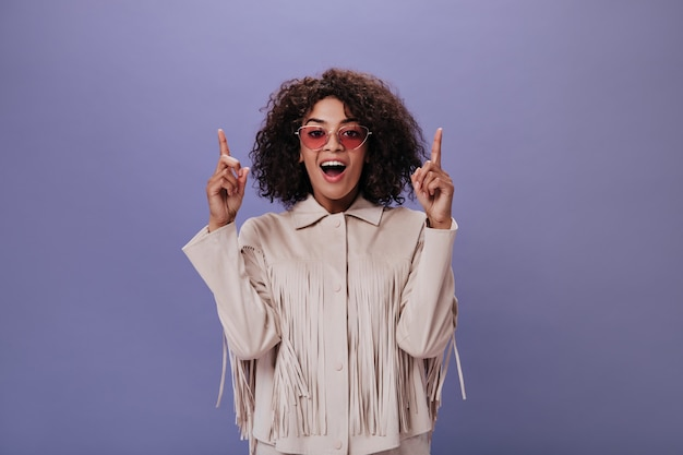 Woman in glasses looks at front and shows her fingers up to place for text on purple wall