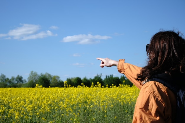 Woman in glasses points to the flowers with her hand