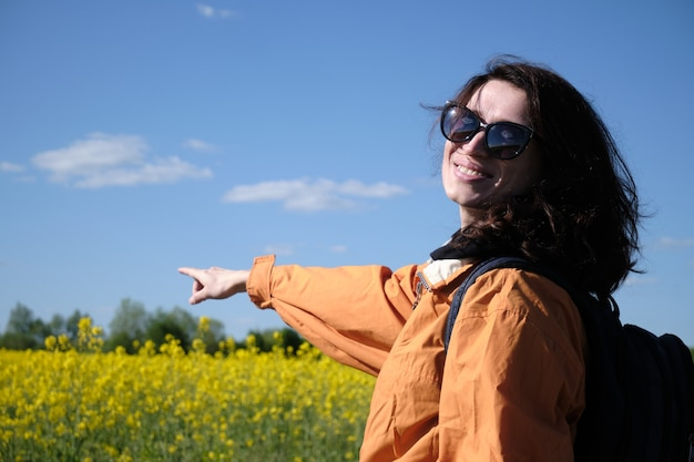 Woman in glasses points to the flowers