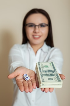 Woman in glasses shows dollars and dice