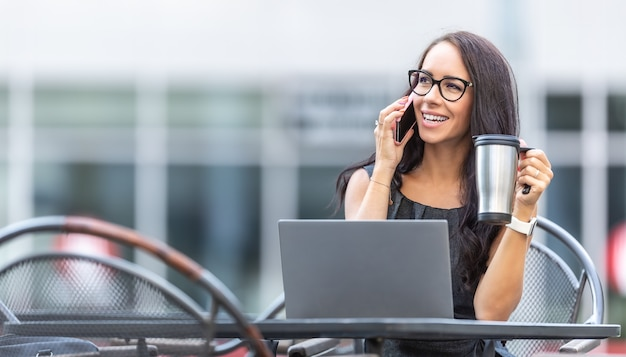 Woman in glasses talks on a phone smiling, holding portable coffee mug and working outside the office building.