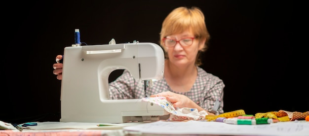 Woman in glasses using sewing machine or threading on dark background
