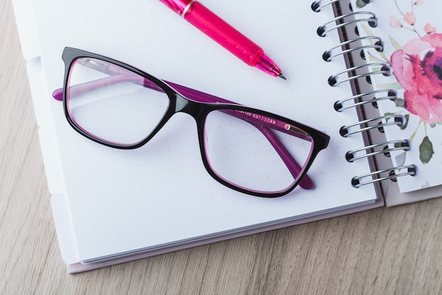 Woman glasses with planner and pencils