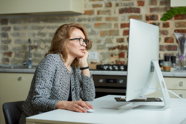 A woman in glasses works remotely on a desktop computer in her studio. a female boss listening reports of employees at a video conference at home.