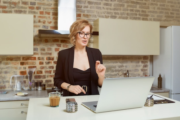 A woman in glasses works remotely on a laptop in her kitchen. a blond girl with braces gesticulating discusses with her colleagues on a video conference at home.