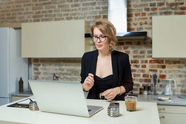 A woman in glasses works remotely on a laptop in her kitchen. a girl discusses with her colleagues on an online business briefing at home.