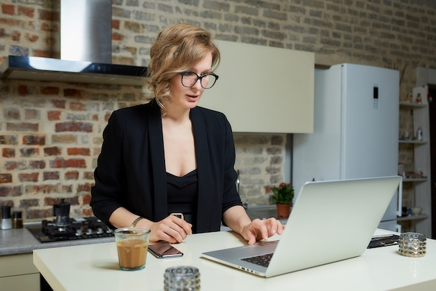 A woman in glasses works remotely on a laptop in her kitchen. a serious girl browsing news on the internet at home. .