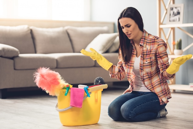 Woman in gloves is sitting confused near the bucket. cleaning concept