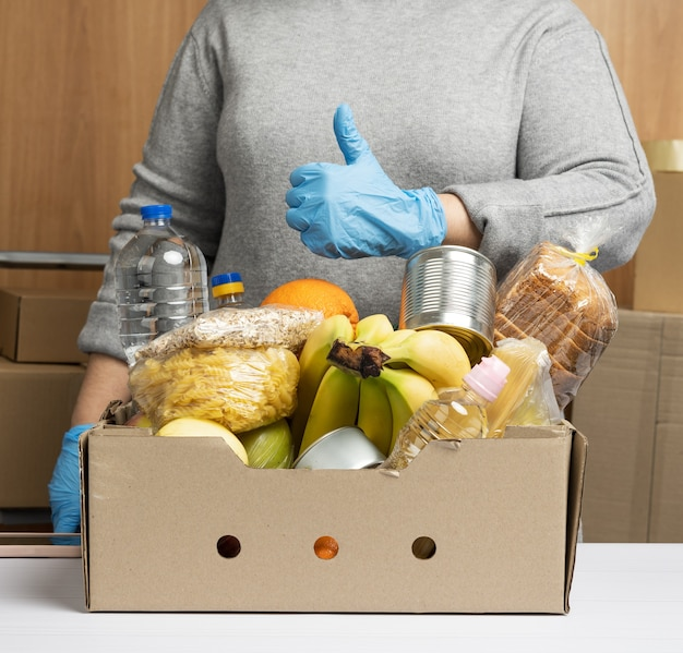 Woman in gloves keeps collecting food, fruits and things and a cardboard box for helping those in need, the concept of help and volunteering.