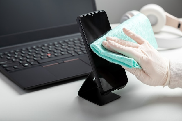 Woman in gloves uses antiseptic spray to clean smartphomeon work space. disinfection phomeand laptop keyboard by alcohol disinfectant by woman in glowes on workplace office desk. long web banner.