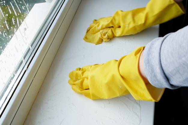 여자 장갑 창턱 세척. 창 청소 서비스 개념입니다.