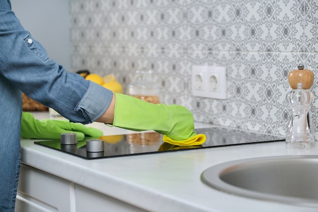 Woman in gloves with rag cleaning kitchen, washing electric hob on countertop of kitchen furniture
