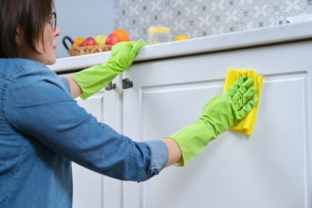 Woman in gloves with rag washing, cleaning, polishing furniture doors on kitchen