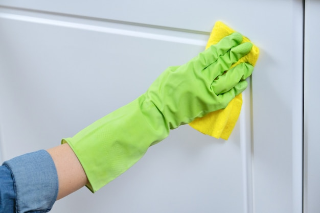 Woman in gloves with rag washing, cleaning, polishing furniture doors