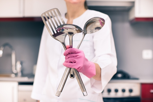 Woman in glowes holking metal tools, house cleaning service