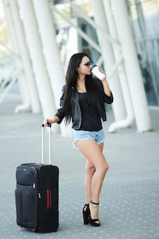 Женщина отправляется с багажом в международный аэропорт львова и пьет кофе.