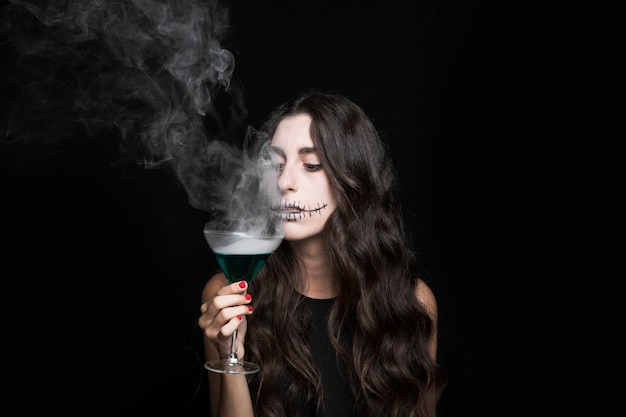 Woman goblet smelling at vapor of smoking turquoise liquid