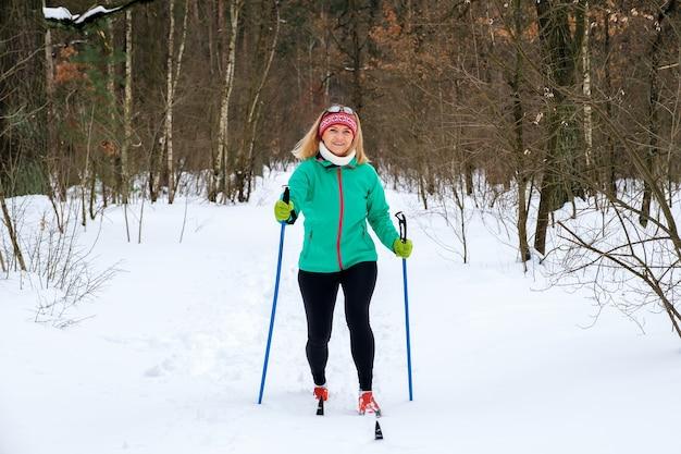 女性は森の中で冬にクロスカントリースキーに行きます