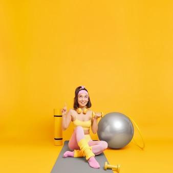 Женщина занимается спортом в фитнес-студии, показывает вверх, поднимает гантели, демонстрирует пространство для копирования