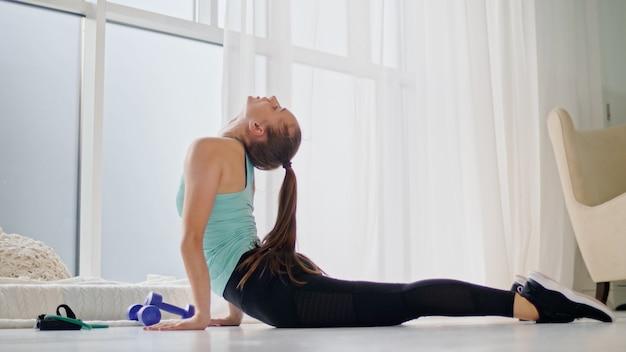 女性は家でスポーツとフィットネスのために行きます。健康的な生活様式。