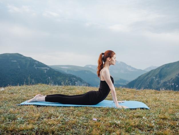 女性は屋外の新鮮な空気の山の草でスポーツに行きます。