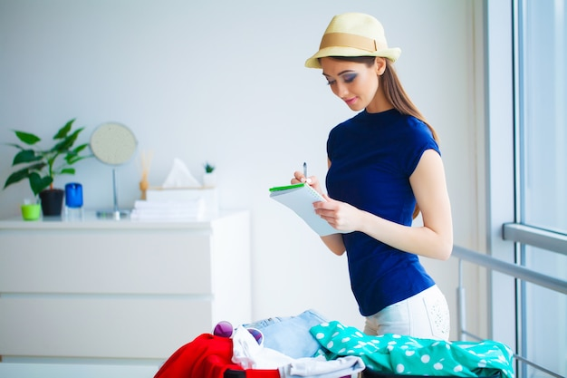 Woman goes on vacation and puts on clothes in suitcase