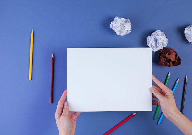 Woman going to draw with colored pencils on blue with crumpled paper balls