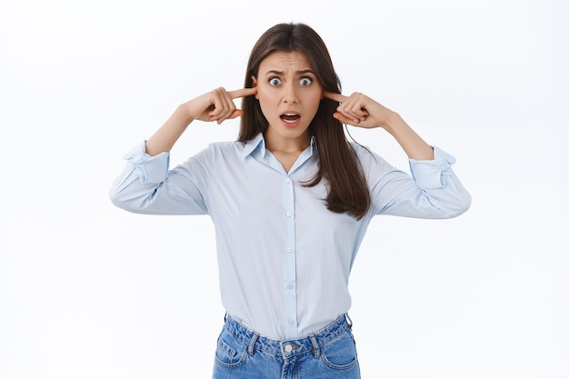 이웃을 연주하는 시끄러운 끔찍한 음악으로 미쳐가는 여자, 짜증나고 불쾌한 찡그린 얼굴로 소음에 대해 불평, 귀에 손가락을 꽂는 큰 불편함, 흰 벽