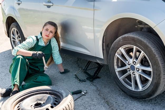 길가에 손상된 바퀴를 변경하려고하는 여자