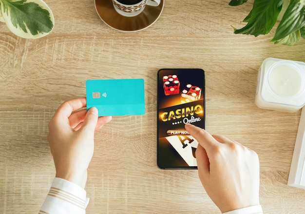居間からオンラインカジノをプレイし、クレジットカードを持って支払う女性。