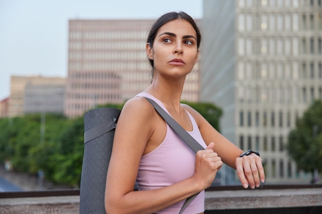 Женщина, собирающаяся заниматься продвинутой йогой, проверяет результаты тренировок на фитнес-часах, позирует в городе