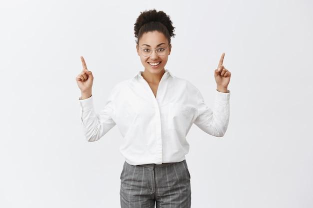 キャリアのはしごを上がる女性。魅力的な成功した、幸せな実業家、暗い肌、人差し指を引き上げ、上向きに、灰色の壁に広く笑みを浮かべて