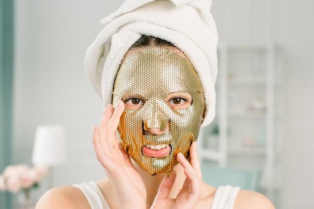 Женщина золотая маска. красивая молодая женщина в белом полотенце на голове с золотой кожей косметики, глядя на камеру. уход за кожей красоты и лечение