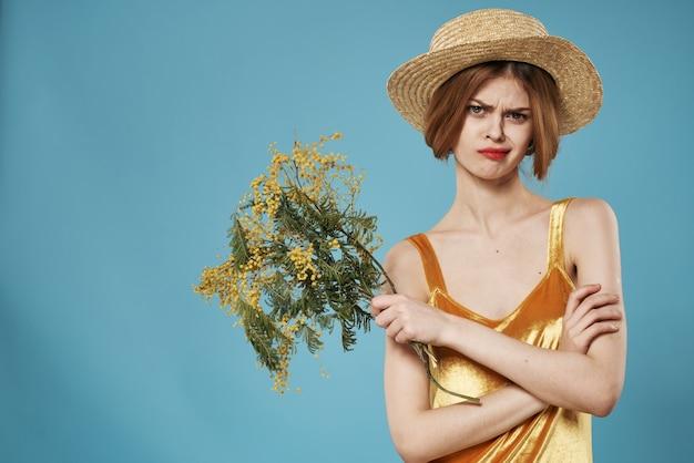 Женщина золотое платье букет праздника цветов мимозы. фото высокого качества