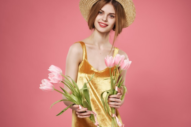 花の花束の装飾ピンクの背景の豪華な女性の黄金のドレス