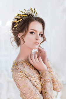 Woman in golden evening gawn and crown poses in luxury white room