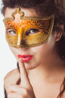 Woman in golden mask gesturing silence