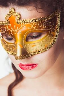 Donna in maschera d'oro con gli occhi chiusi
