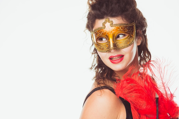 Woman in golden mask with feathers