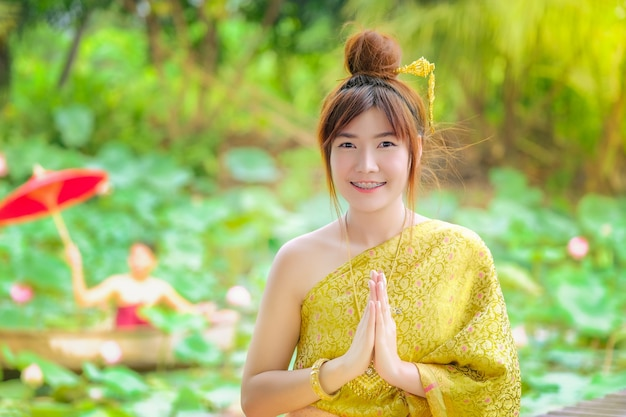 The woman in the golden thai dress is good morning in the lotus garden.