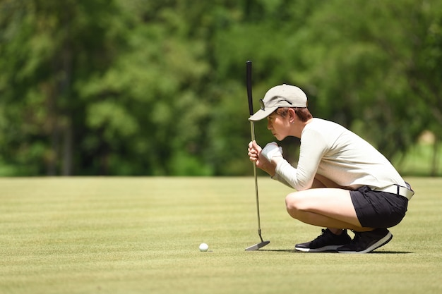 Линия проверки гольфиста женщины для установки шара для игры в гольф на зеленой траве