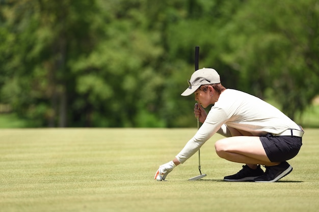 Woman golfer check line for putting golf ball on green grass
