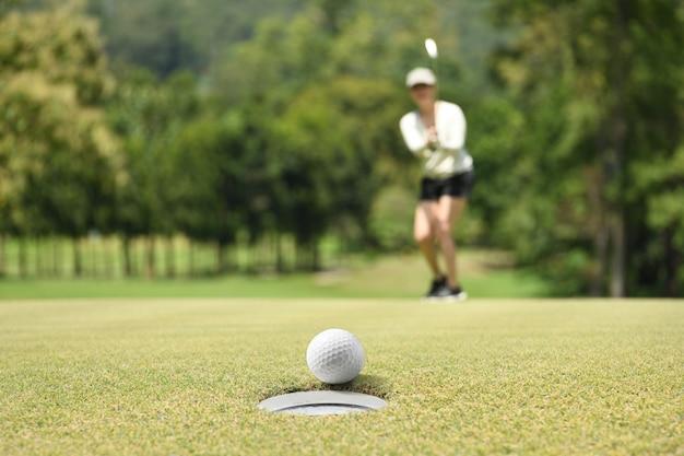 Женщина гольфист аплодисменты после мяч для гольфа на зеленый гольф