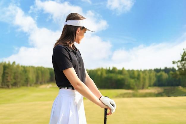 女性ゴルファーがクラブハウスに向かってフェアウェイショットを打つ。