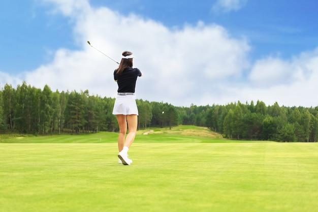 Игрок в гольф бьет по воротам клуба.