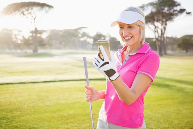 彼女の携帯電話を探している女性ゴルファー