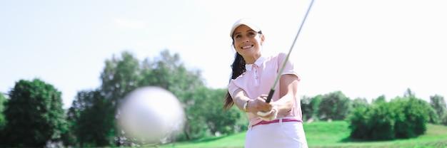 Игрок в гольф женщина делает удар клюшкой по мячу.