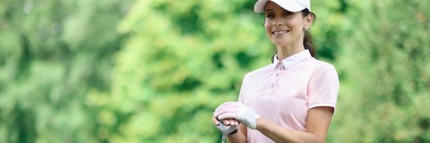 여자 골퍼는 골프 코스 옆에 서