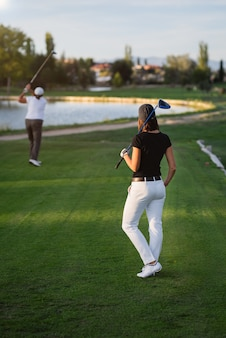 Woman golfer waiting her turn to tee of