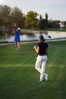 여자 골퍼 티 박스 fron 떨어져 그녀의 차례를 기다리고. 아름 다운 골프 코스에 화창한 날에 그녀의 드라이버 골프 클럽 여성 서 뒤에서 볼.